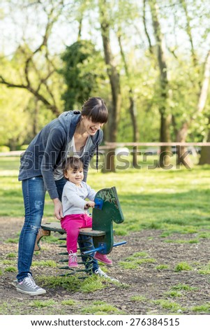 Mother and Daughter playing in the park on spring day... Selective focus... - stock photo