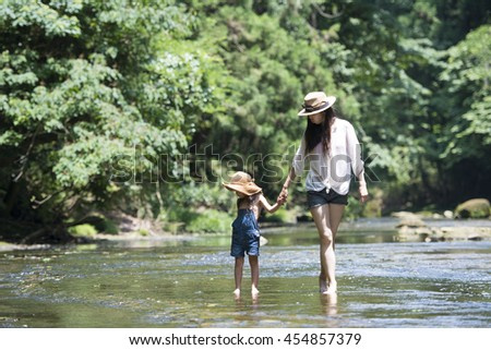 Mother and daughter playing in the river