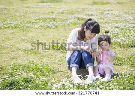 Mother and daughter playing in the spring meadow