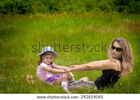 mother and daughter playing on grass. spring day - stock photo