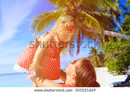 mother and daughter playing on summer tropical beach - stock photo