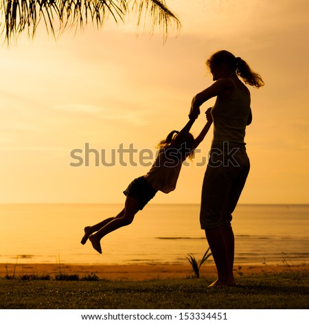 mother and  daughter playing on the beach - stock photo