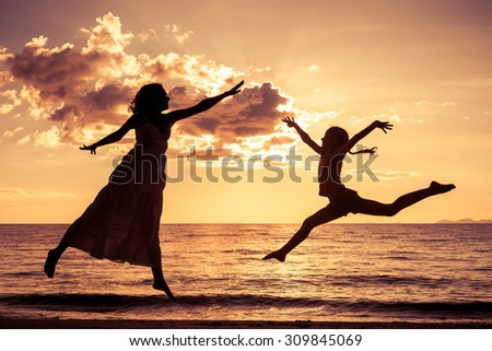mother and  daughter playing on the beach at the sunset time - stock photo