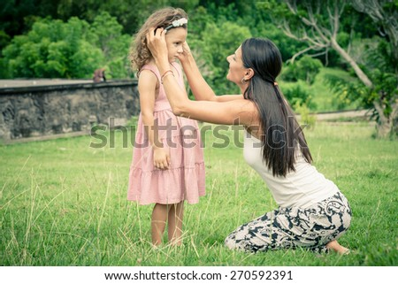 Mother and daughter playing on the grass at the day time. Concept of friendly family. - stock photo