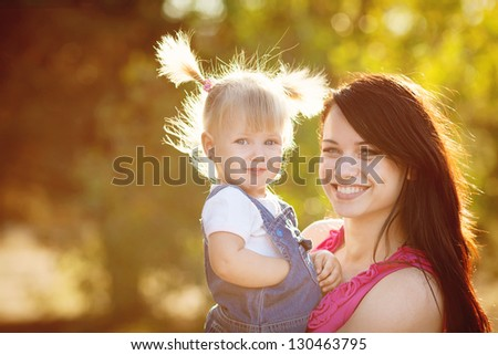 Mother and daughter playing outdoors in summer - stock photo