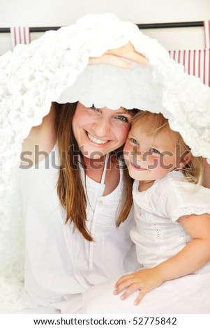 Mother and daughter playing peek-a-boo in bed. Shallow DoF.  Focus on mother.