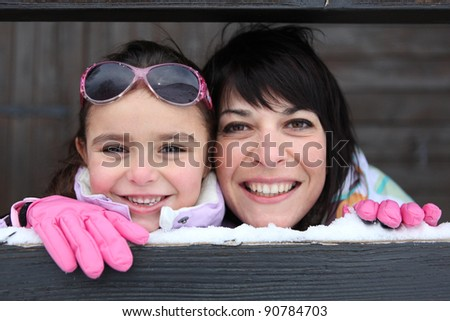 Mother and daughter playing snow - stock photo