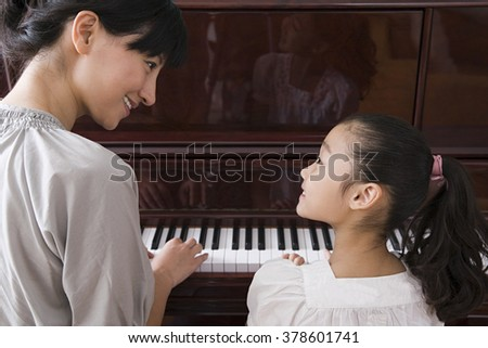 Mother and daughter playing the piano - stock photo
