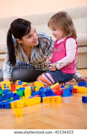 mother and daughter playing together at  home - stock photo