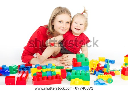 Mother and daughter playing together building blocks over white - stock photo
