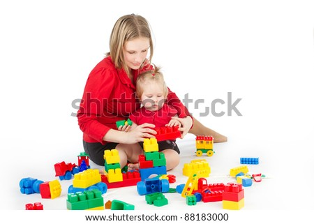 Mother and daughter playing together building blocks over white background - stock photo