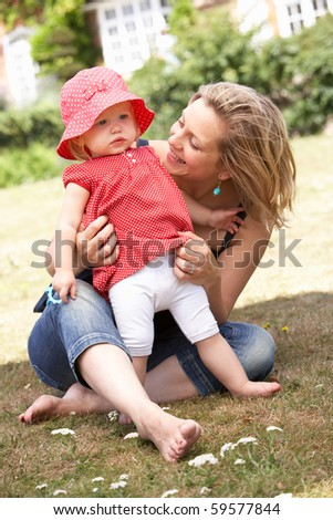 Mother And Daughter Playing Together In Garden At Home - stock photo