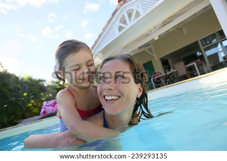 Mother and daughter playing together in pool - stock photo