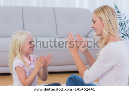 Mother and daughter playing together in the living room - stock photo