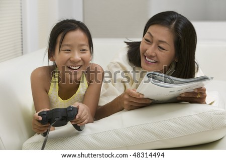 Mother and Daughter Playing Video Game and Reading on Couch - stock photo