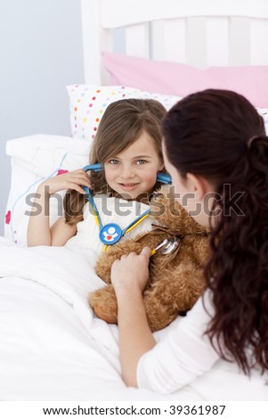 Mother and daughter playing with a stethoscope in bed