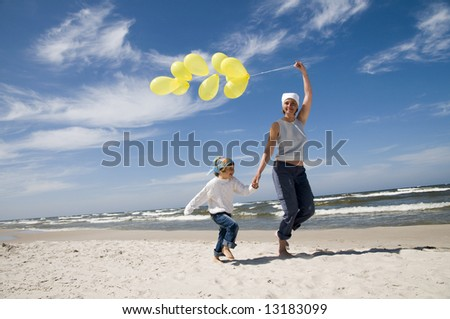Mother and daughter playing with balloons on the beach - stock photo