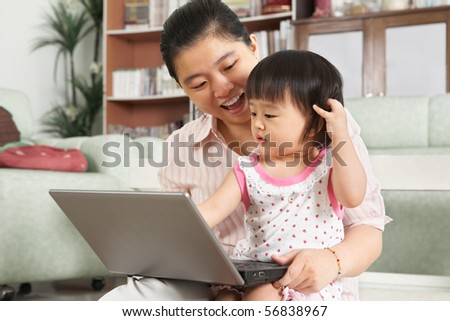 Mother and daughter playing with laptop together at home