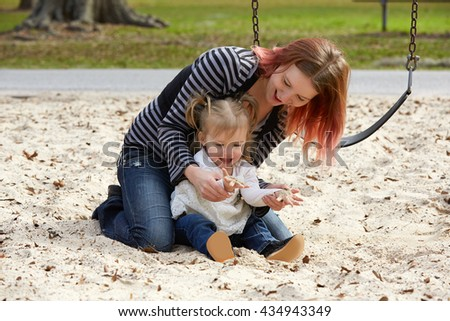 Mother and daughter playing with sand having fun at the park playground - stock photo