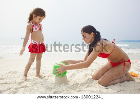 Mother and daughter playing with sand on sea coast