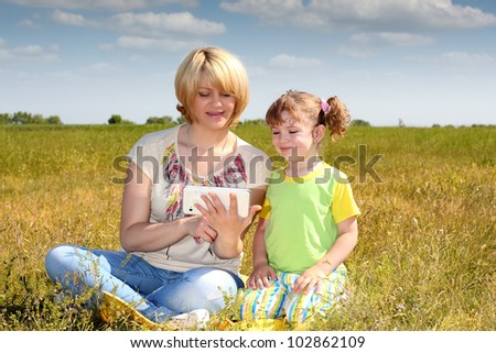 mother and daughter playing with tablet - stock photo