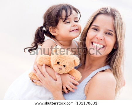 Mother and daughter portrait with a teddy bear - stock photo