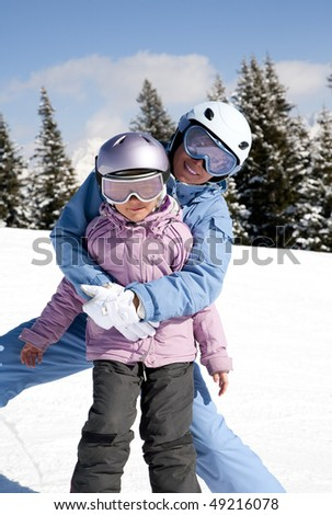 Mother and daughter posing happily against mountains - stock photo