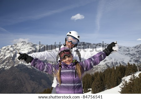 Mother and daughter posing happily against mountains