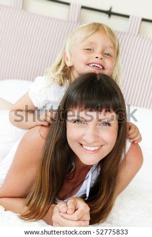 Mother and daughter posing happily in bed. Shallow DoF. Focus on mother. - stock photo