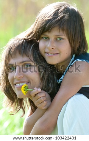 Mother and daughter posing happily on nature background. The girl has hold of yellow flower in her hand. - stock photo