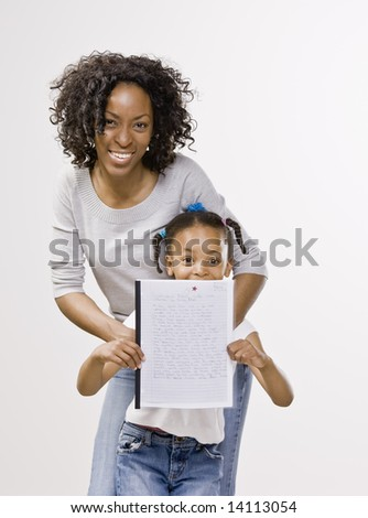 Mother and daughter posing with school report - stock photo