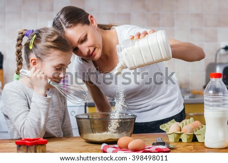 Mother and daughter pouring flour into bowl - stock photo