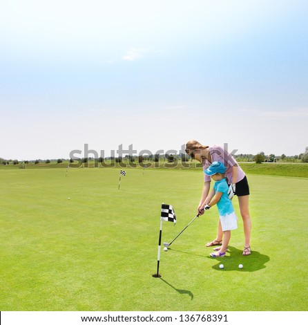 Mother and daughter practicing to hit the ball at the course - stock photo