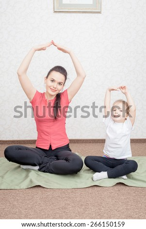 Mother and daughter practicing yoga at home - stock photo