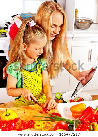Mother and daughter prepare recipe at kitchen.