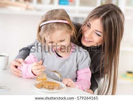 Mother and daughter preparing breakfast. They smear honey over the peanut butter on bread. - stock photo