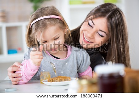 Mother and daughter preparing breakfast. They smear honey over the peanut butter on bread.
