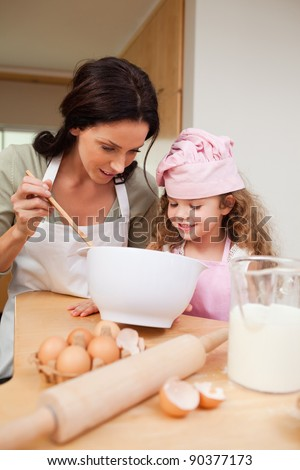 Mother and daughter preparing cookies together - stock photo