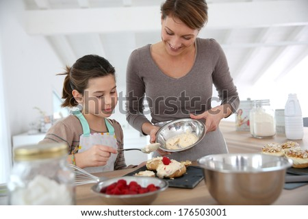 Mother and daughter preparing cream puffs - stock photo