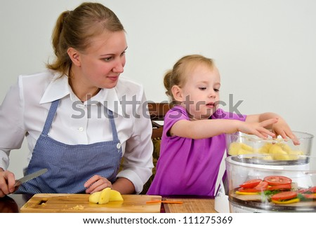 Mother and daughter preparing food in steamer. - stock photo