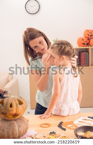 Mother and daughter preparing for the Halloween - stock photo