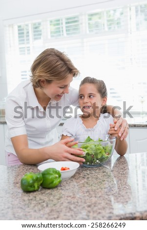 Mother and daughter preparing salad at home in kitchen