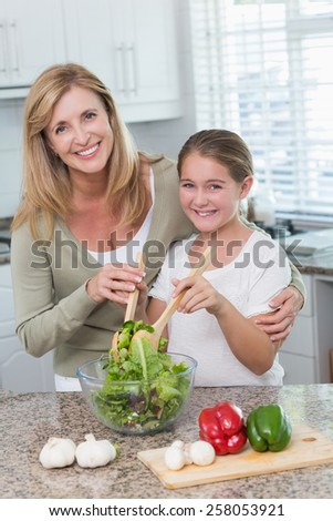Mother and daughter preparing salad together at home in the kitchen - stock photo