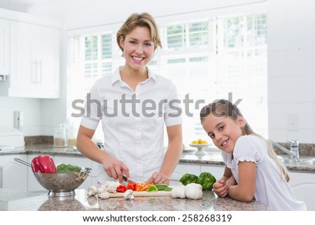 Mother and daughter preparing vegetables at home in kitchen - stock photo