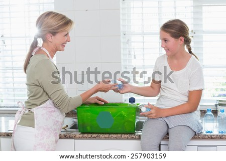Mother and daughter putting bottles in recycling box at home in the kitchen - stock photo