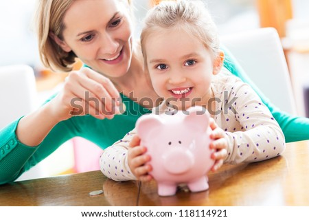 Mother and daughter putting coins into piggy bank - stock photo