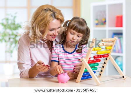 Mother and daughter putting coins into piggy bank. Child counting and saving money. - stock photo