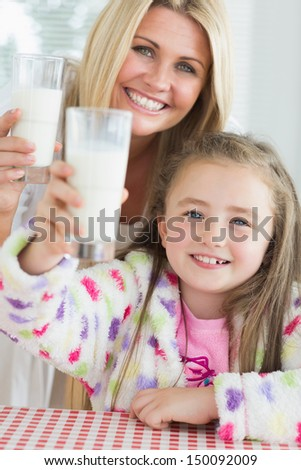 Mother and daughter raising milk glasses in kitchen - stock photo