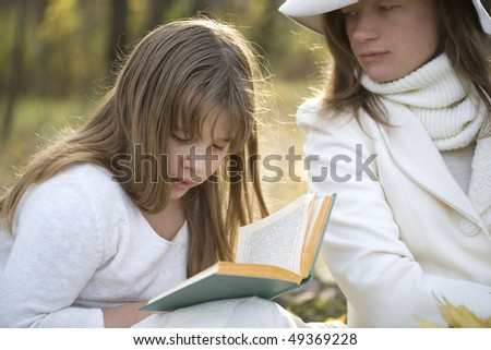 Mother and daughter read book in the park