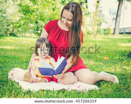 Mother and daughter reading a book outdoors on grass at park